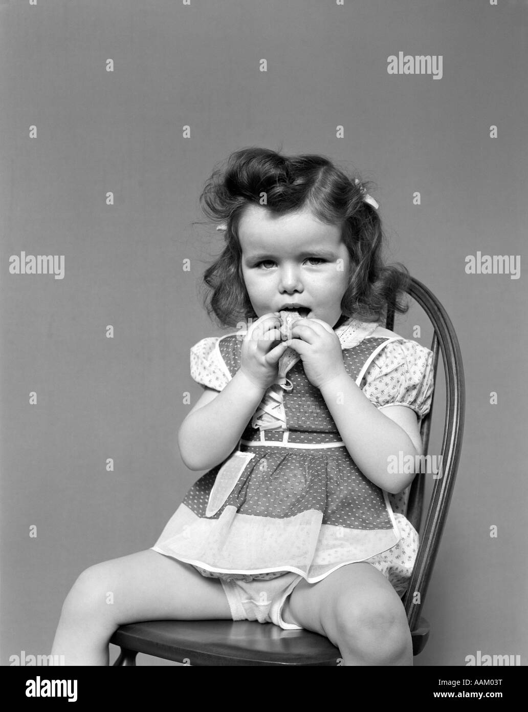 Black child sitting in chair - 1930s Toddler Girl Sit In Wooden Chair Polka Dot Dress Showing Underpants Eating A Cookie With Both Hands Vintage
