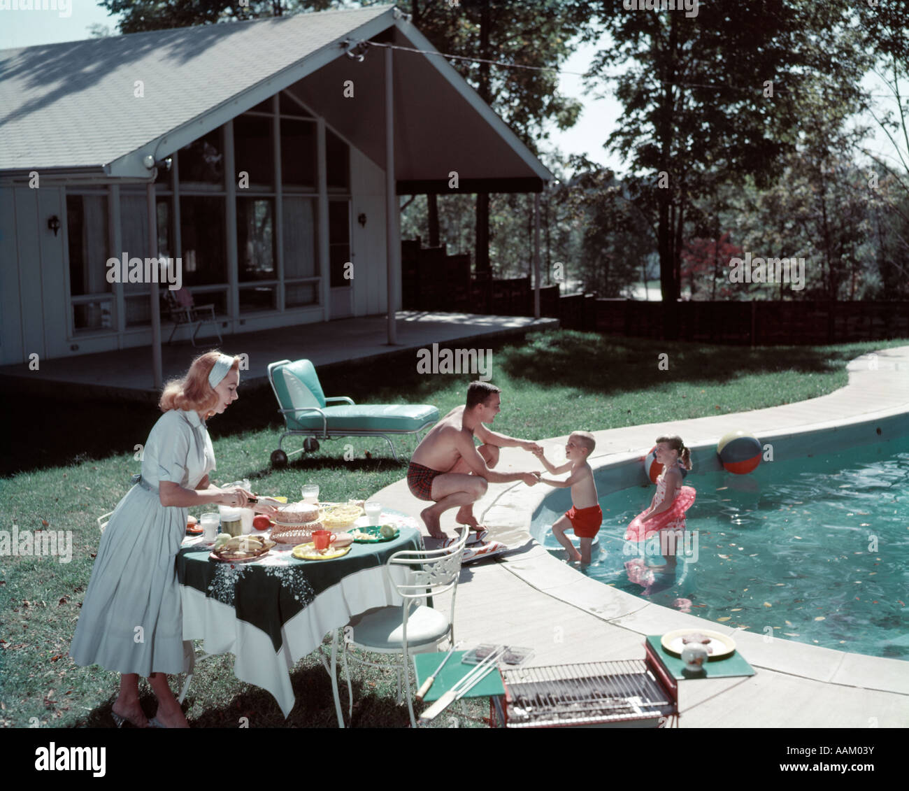 1950s family of 4 backyard swimming pool house mom serving food
