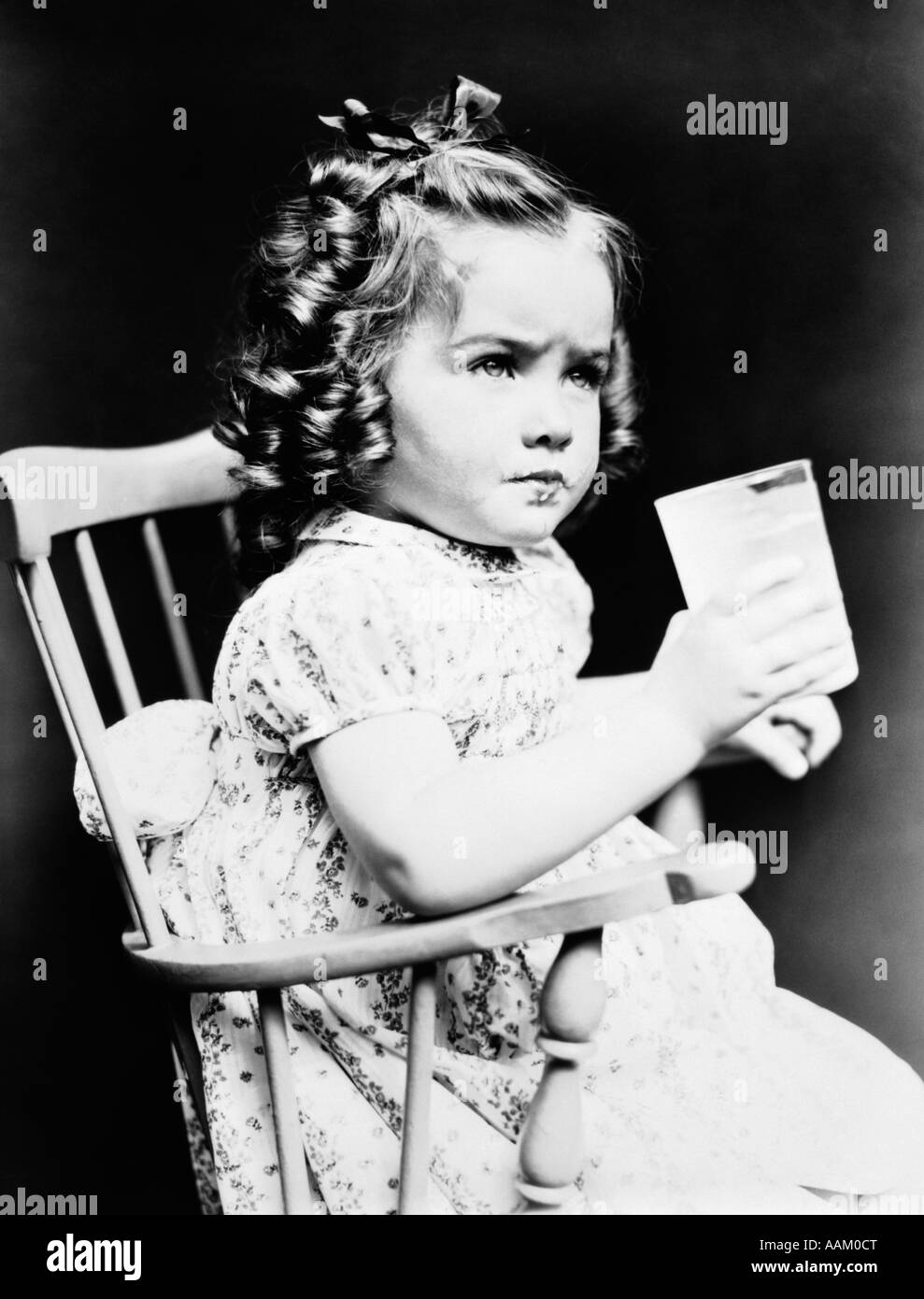 Black child sitting in chair - 1930s Child Girl Sitting In High Chair Holding Glass Of Milk Serious Look Bow In Hair Baloney Curls