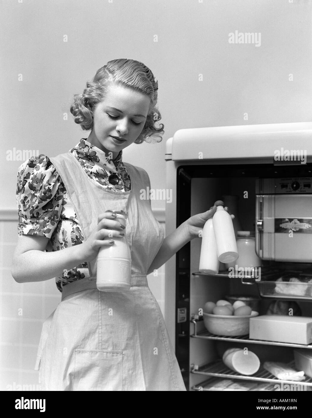 White tudor apron - 1930s Woman Wearing A White Apron Taking Milk Out Of The Refrigerator Stock Image