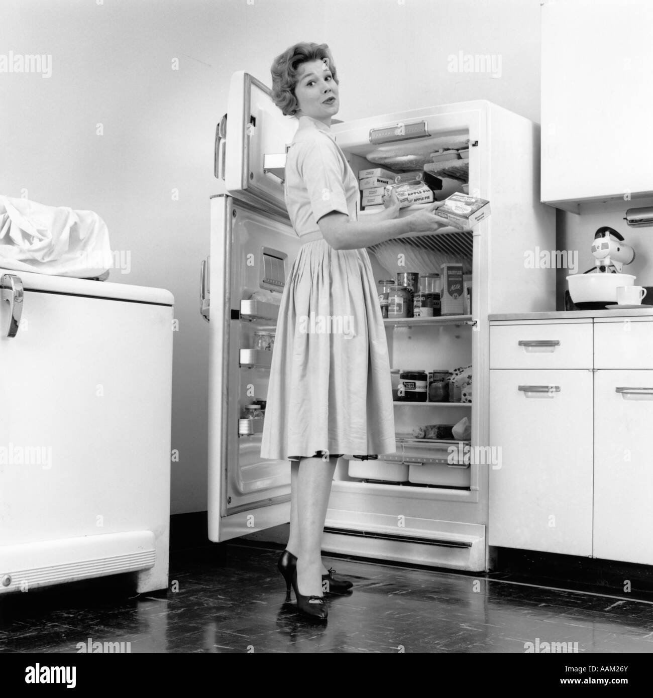 Vintage Kitchen Photography: 1950s WOMAN STANDING IN KITCHEN BY OPEN REFRIGERATOR Stock Photo: 12657650