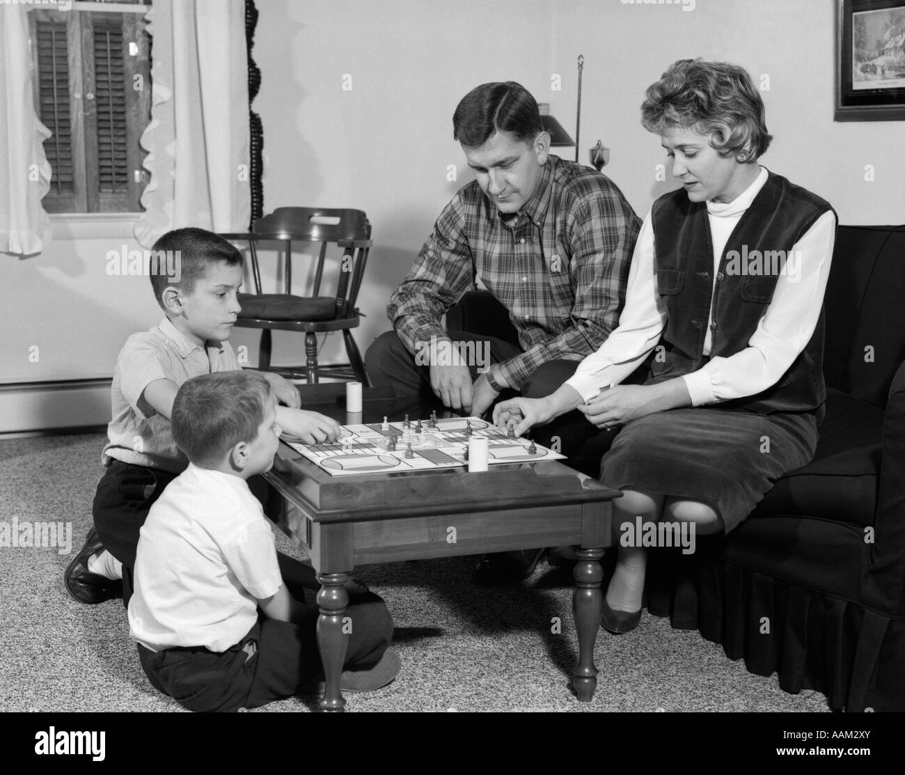 1960s MOTHER FATHER CHILDREN 2 KIDS BOYS PLAYING BOARD GAME PARCHEESI FAMILY FUN SOCIAL LIVING ROOM