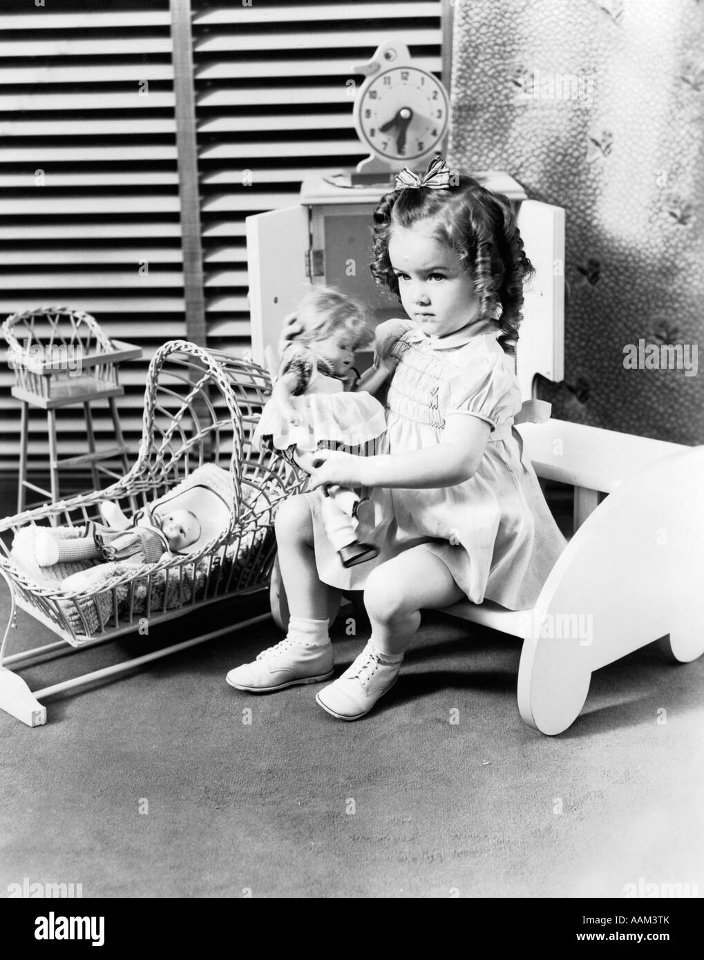 Black child sitting in chair - 1940s 3 Year Old Girl Sitting Holding Baby Doll Toy Cradle Toy High Chair Toy Clock Venetian Blinds