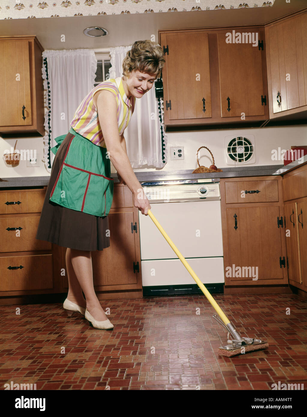 1960s WOMAN IN APRON CLEANING KITCHEN FLOOR WITH SPONGE MOP
