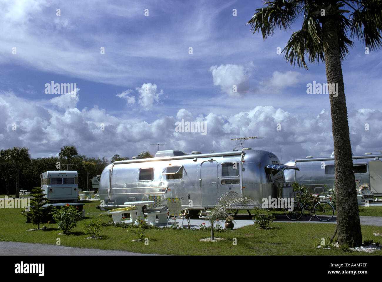 1970 1970s SILVER AIRSTREAM TRAILER IN MOBILE HOME PARK FLORIDA PALM TREE