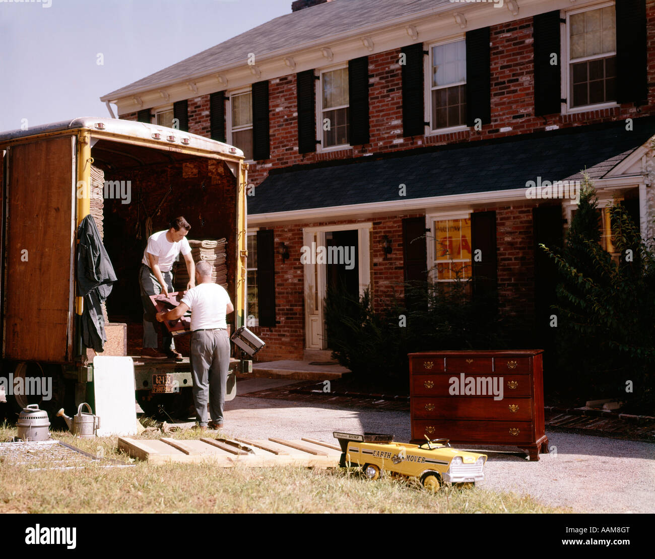 1970s 2 men workers movers load unload back of truck moving van furniture house new brick