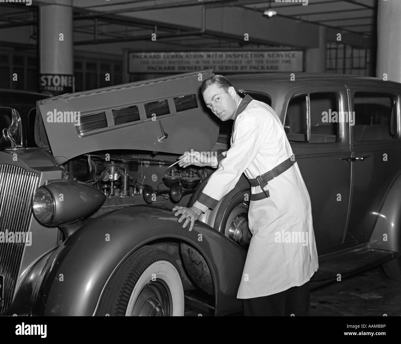 1940s MECHANIC LOOKING AT CAMERA WORKING UNDER HOOD OF CAR WEARING ...