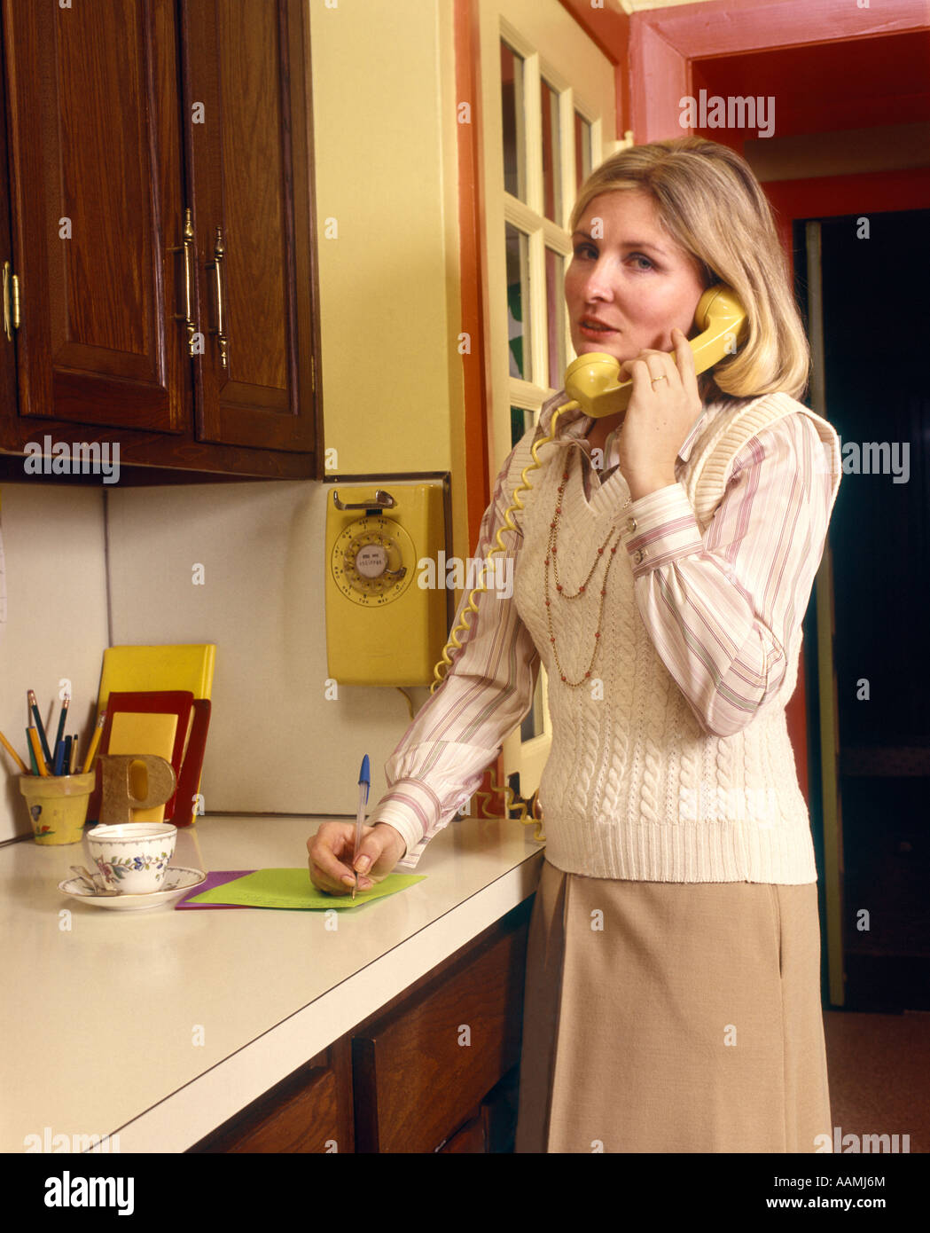 1970 1970s WOMAN HOUSEWIFE TALKING ON YELLOW WALL PHONE IN KITCHEN NOTE PAD  ON COUNTER WRITING