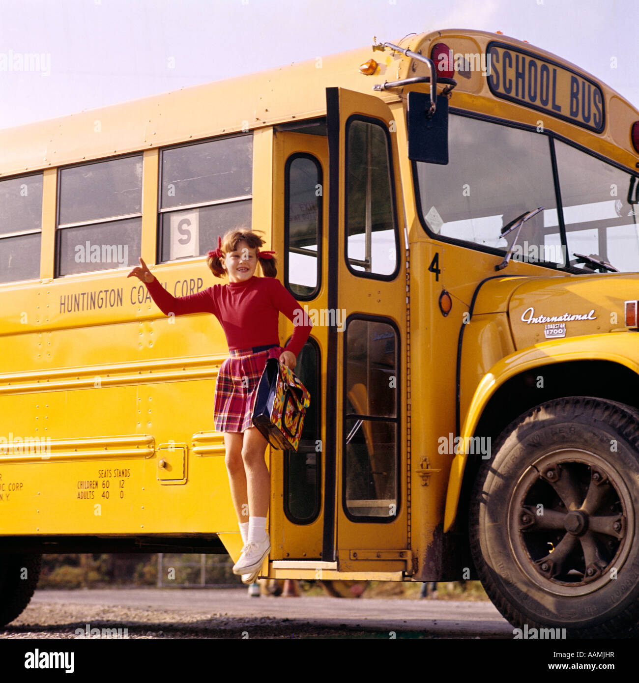1970s 1980s LITTLE GIRL PIGTAILS RED TOP PLAID SKIRT JUMPS OFF YELLOW SCHOOL BUS SNEAKERS BOOK BAG HAPPY FUN COME HOME