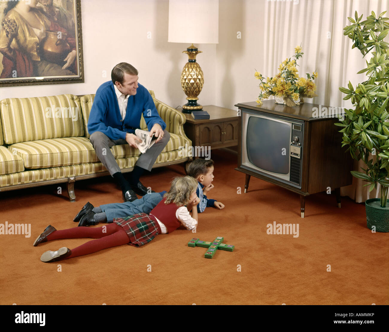 1960s FATHER SITTING ON LIVING ROOM COUCH BROTHER AND SISTER ON FLOOR WATCH  TELEVISION FAMILY MAN BOY GIRL INDOOR