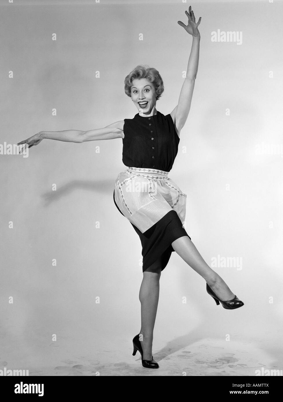White apron ale - 1950s Blonde Woman In Apron Housewife Dancing Kicking Her Leg Looking At Camera Stock Image