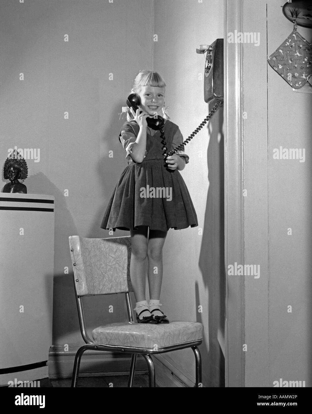 1960s 1950s YOUNG GIRL STANDING ON KITCHEN CHAIR TALKING ON WALL TELEPHONE  LOOKING AT CAMERA