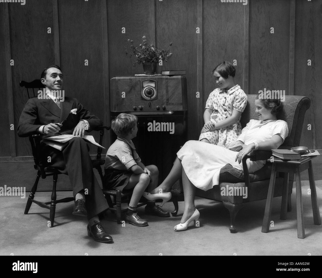Living Room 1940s 1930s 1940s family sitting in living room listening to radio stock