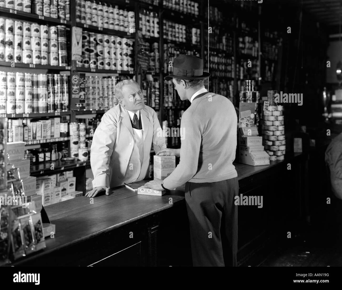 General Store Stock Photos General Store Stock Images: 1930s 1940s TWO MEN CUSTOMER AND CLERK IN GENERAL STORE