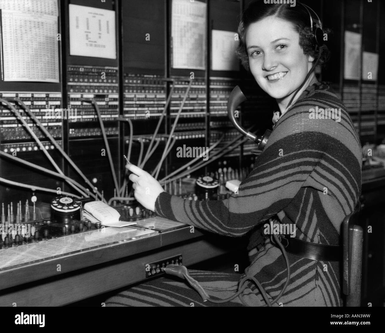 1930s female telephone switchboard operator and supervisor stock 1930s w telephone operator at switchboard looking at camera smiling stock photo
