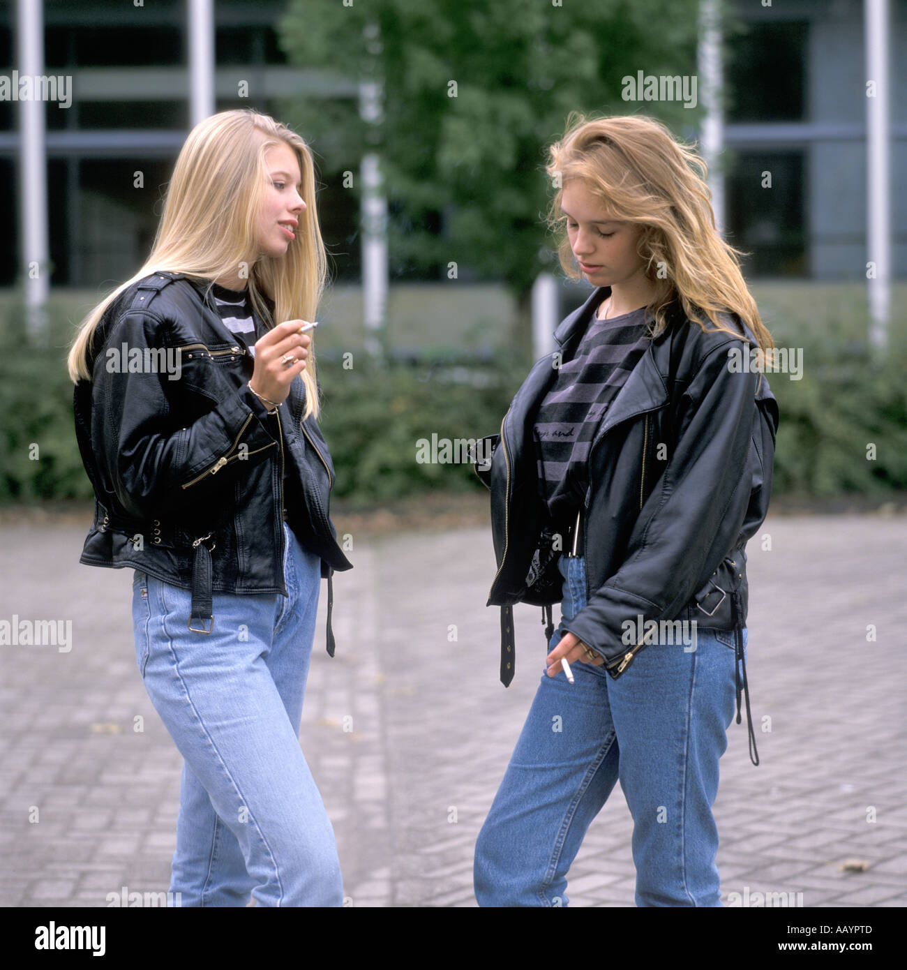 Two teenage girls standing outside smoking a cigarette stock photo