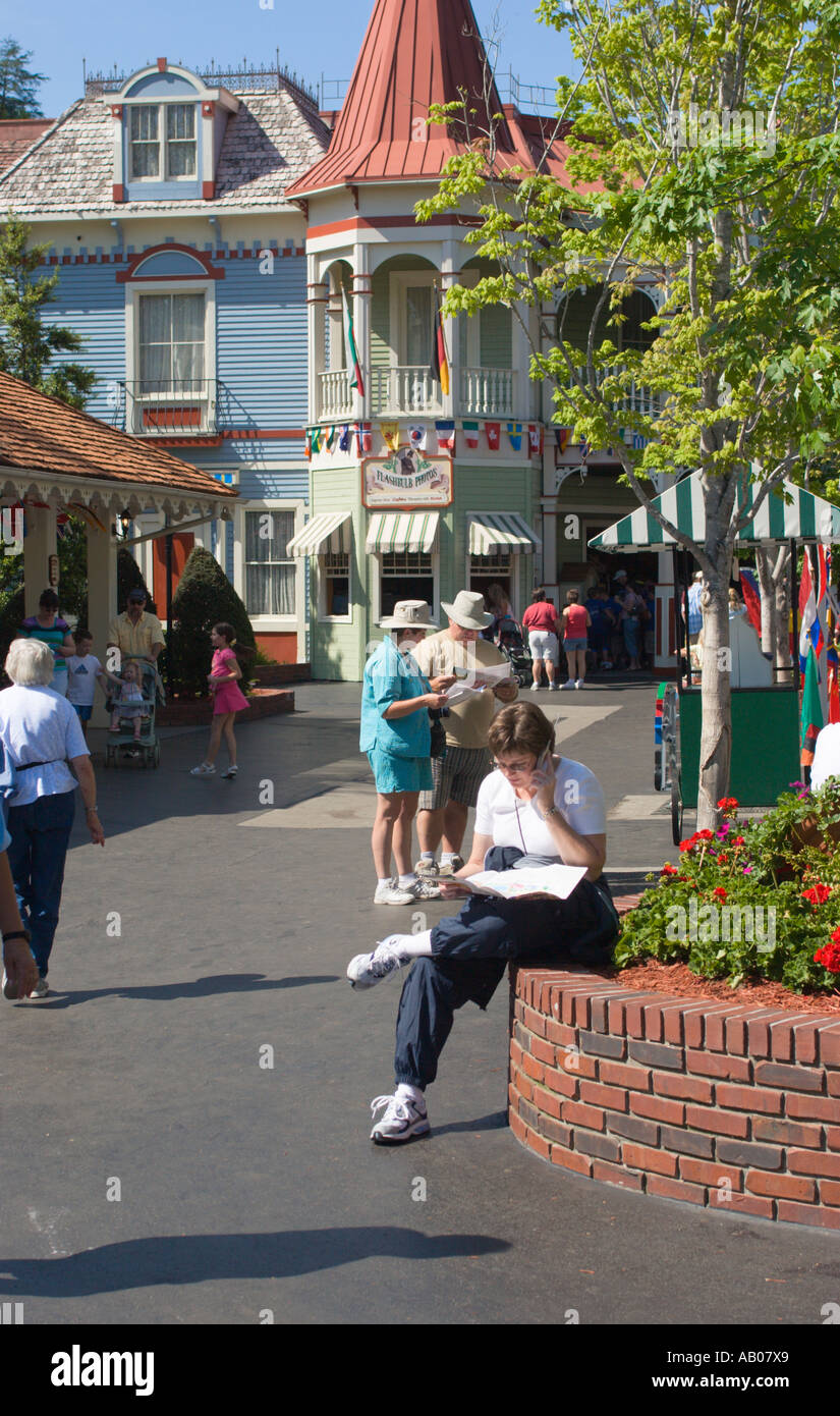 Stock Photo Woman Talks On Cell Phone And Studies Map While Planning Day At Dollywood Theme Park In Pigeon Forge Tennessee Usa
