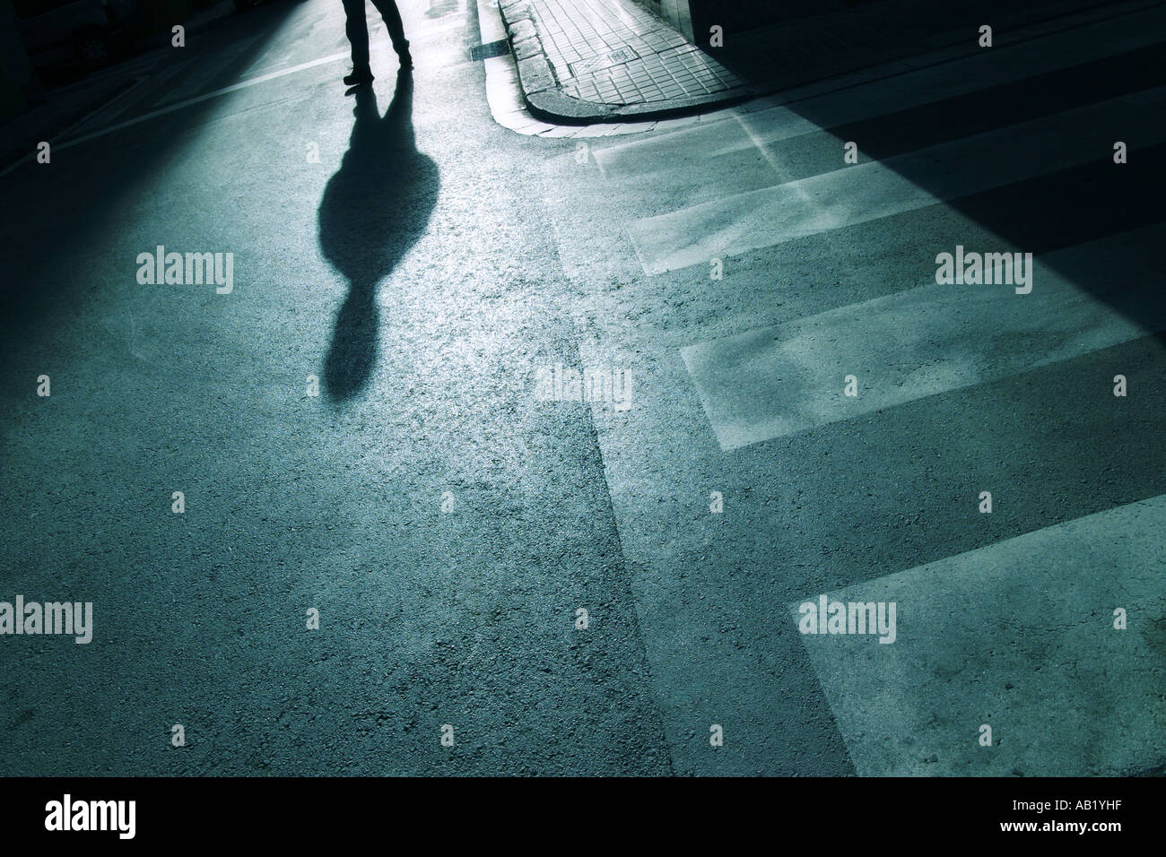 Shadow Of A Person Walking Down The Street Stock Photo