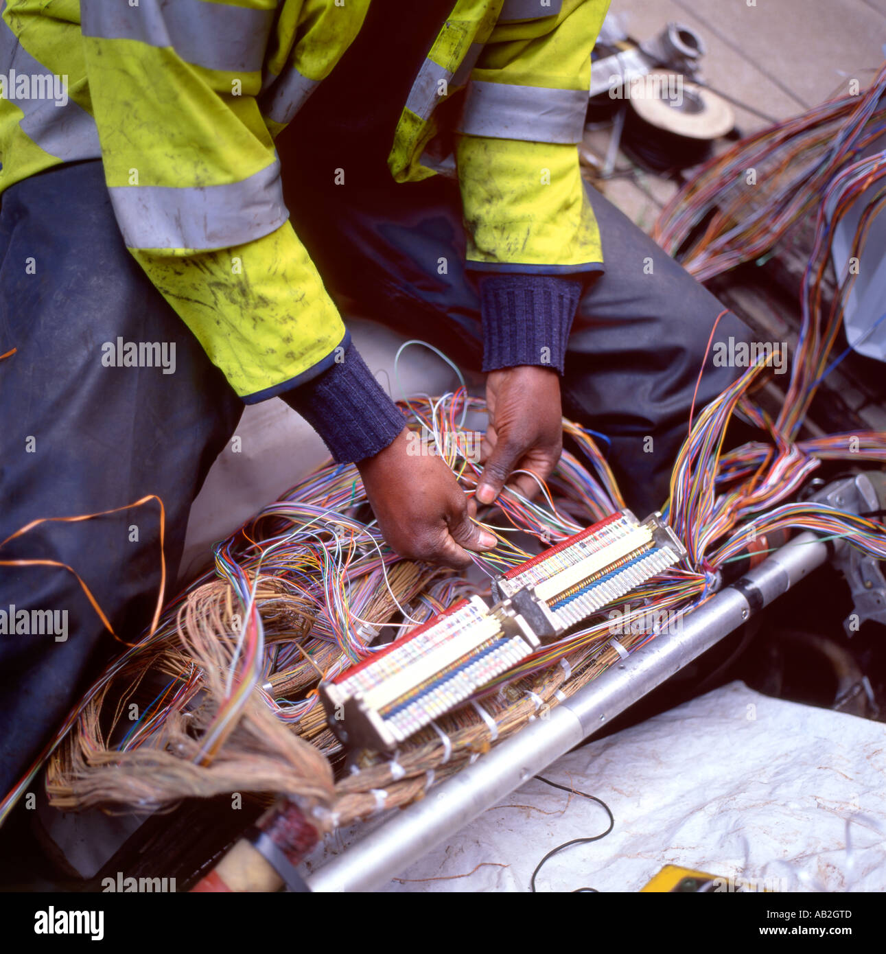 A British Telecom worker working with wiring from under pavement Regent Street London UK : british wiring - yogabreezes.com