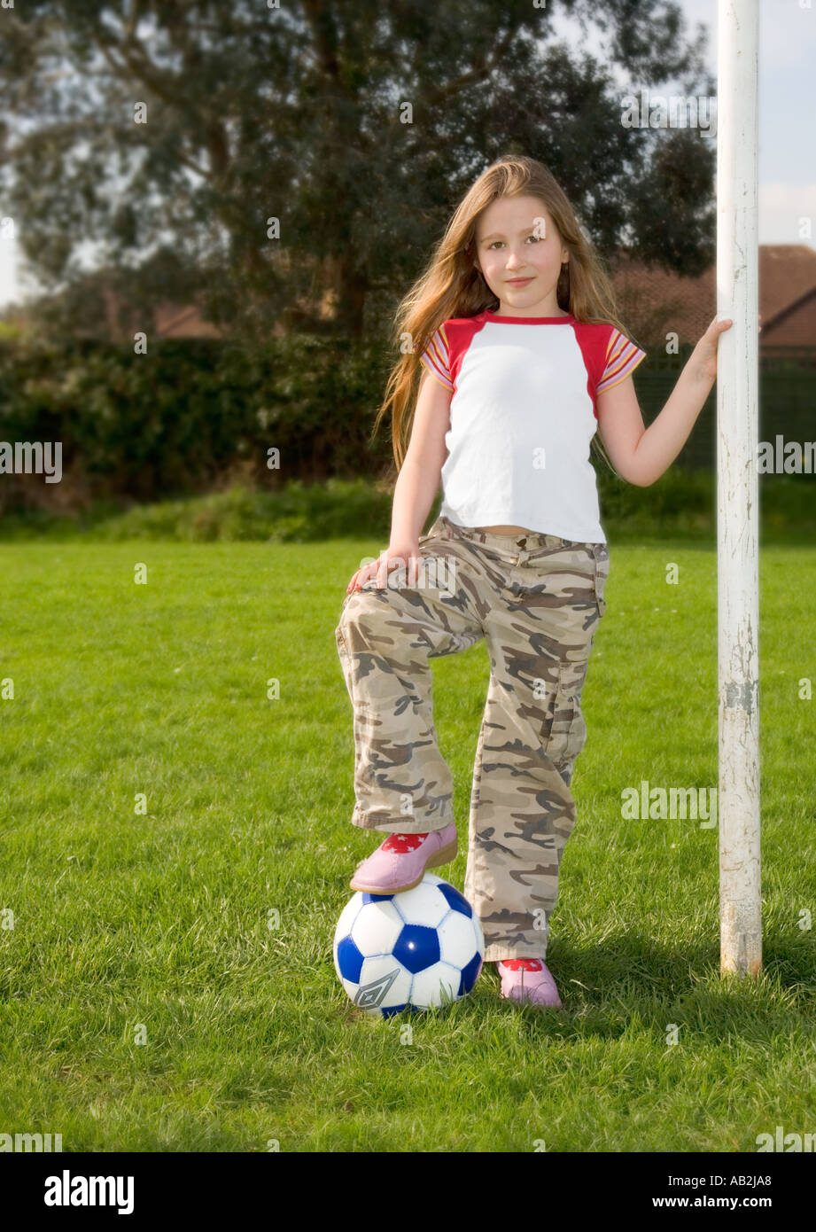 Girl 8 to 10 years old standing with soccer ball next to goal post ...