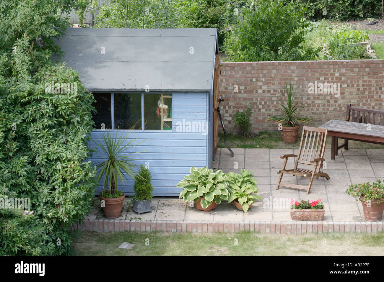 suburban garden with patio shed and plants