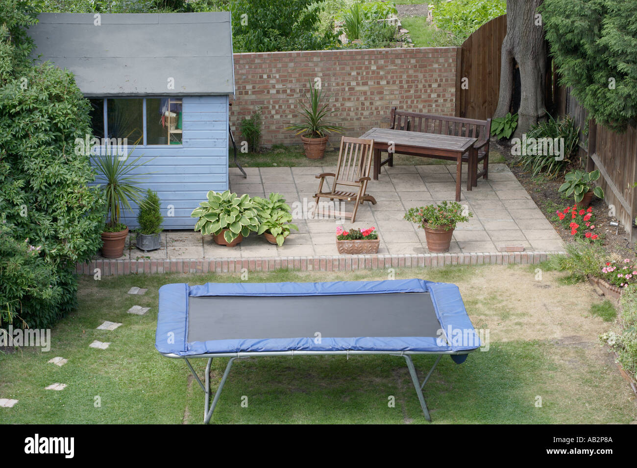 Stock Photo   Suburban Garden With Patio Shed And Trampoline