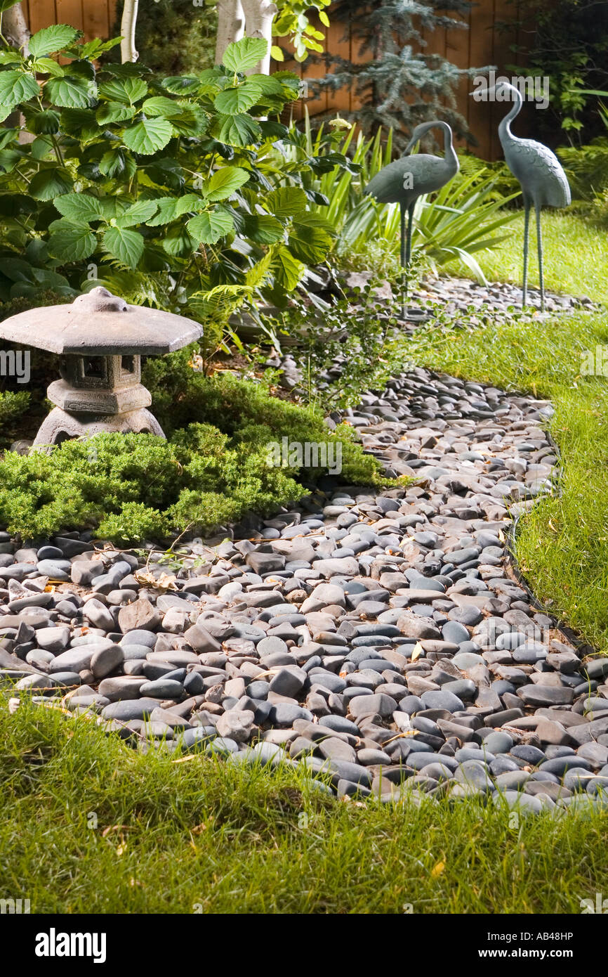 A Backyard Japanese Garden With A Dry Stream Bed Lantern And Crane Statuary