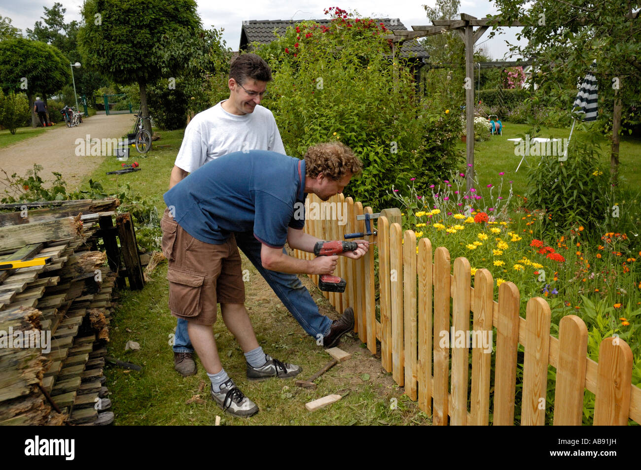 Handymen Building A Garden Fence On Allotments In Germany Stock