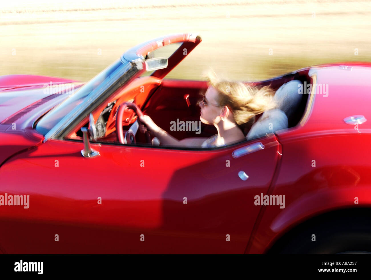 Blond girl driving red convertible corvette stock photo royalty free