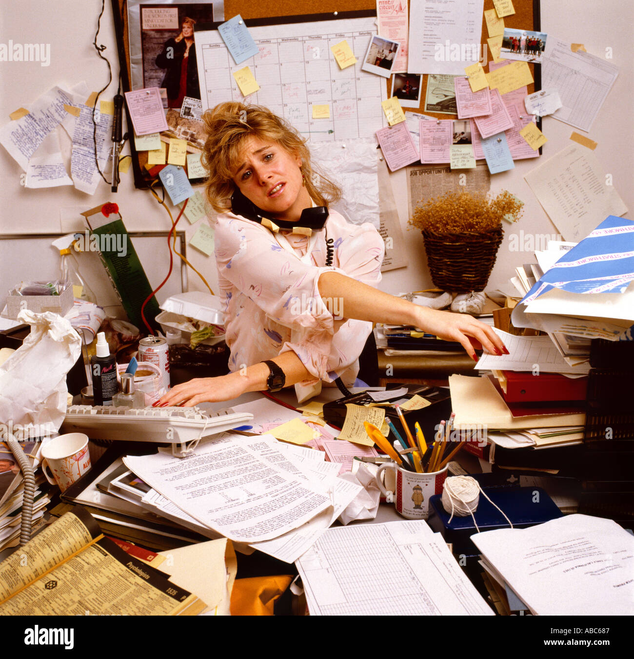 Frustrated office worker on the phone holding stock photo image - Office Environment Frustrated Overworked Office Worker At Her Desk In A Confused Disorganized And Cluttered