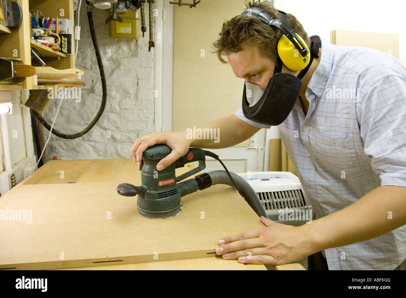 A craftsman uses a random orbit sander with dust extraction to ...