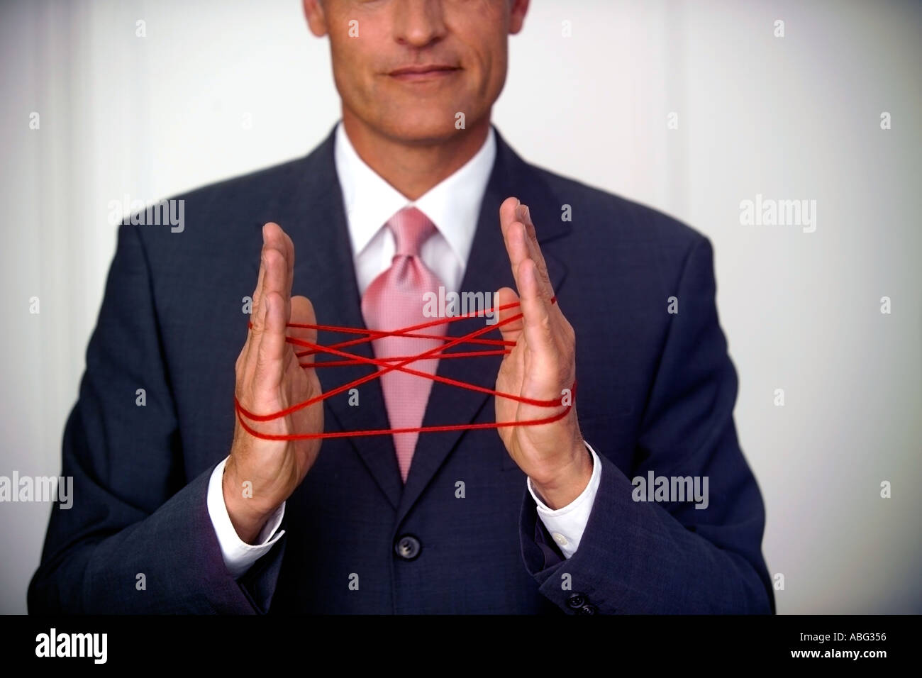 mature businessman doing the cat s cradle with red string stock
