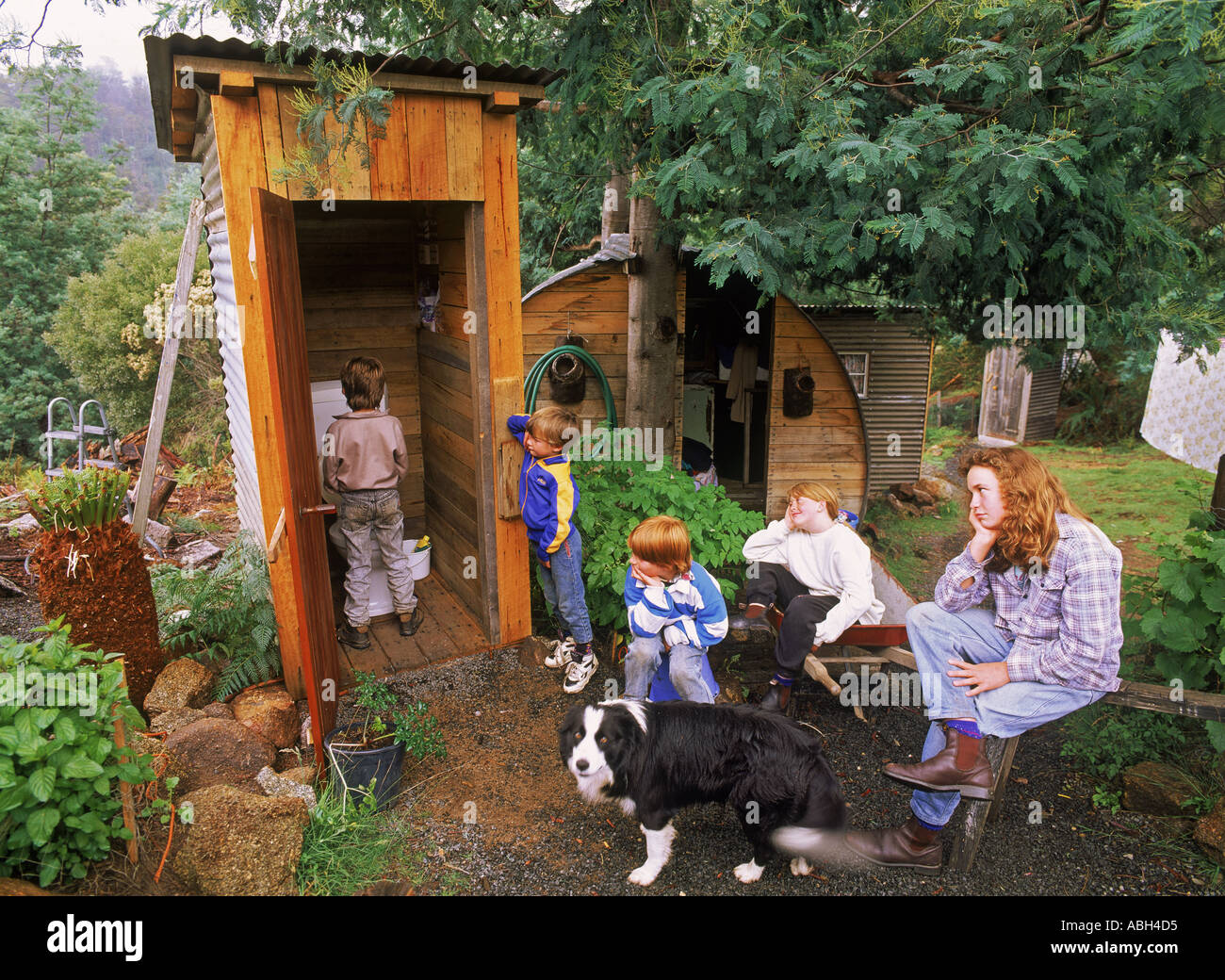 kids and mom waiting to use family dunny or outhouse in country