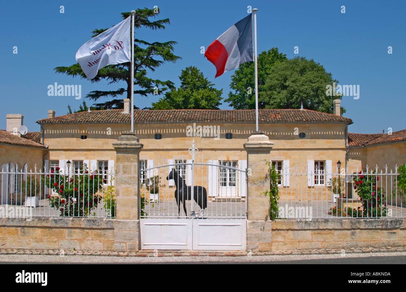 Chateau La Couspaude, the main building, with a white iron fence a ...