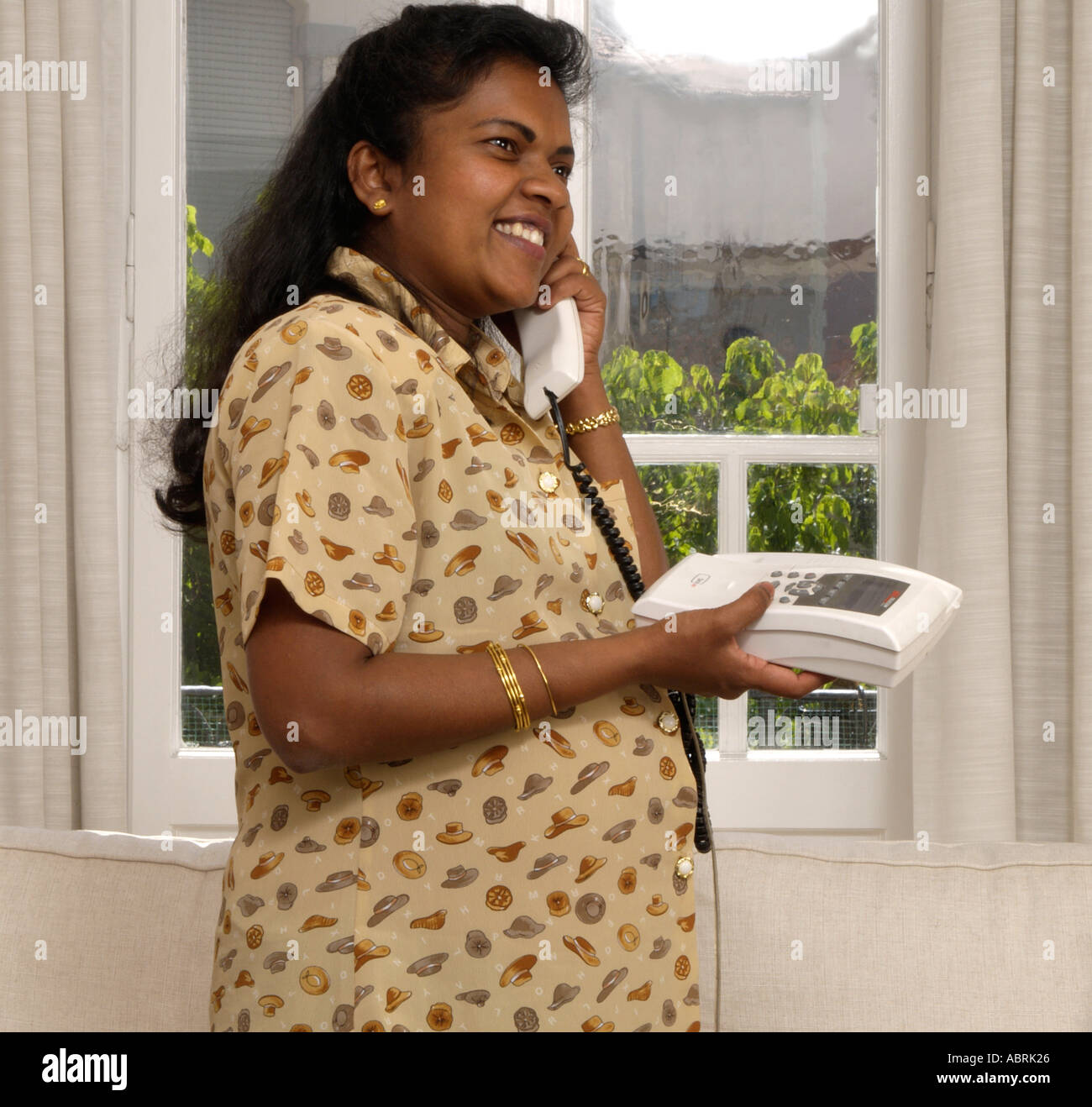 Indian sri lankan woman 8 months pregnant talking on phone for Gardening 8 months pregnant