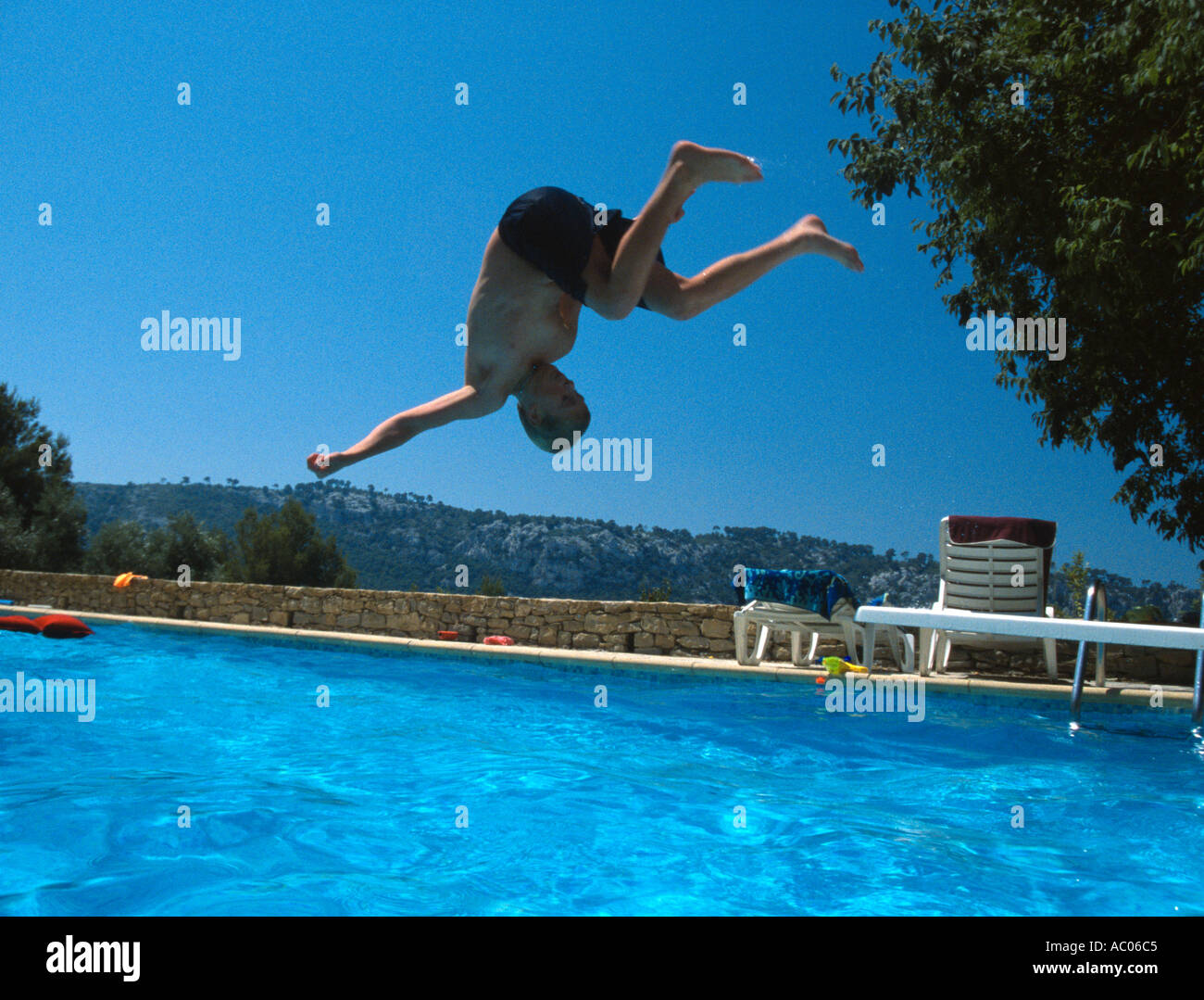 Teenage Boy Somersaulting Off Diving Board Into Swimming Pool Villa Stock Photo Royalty Free