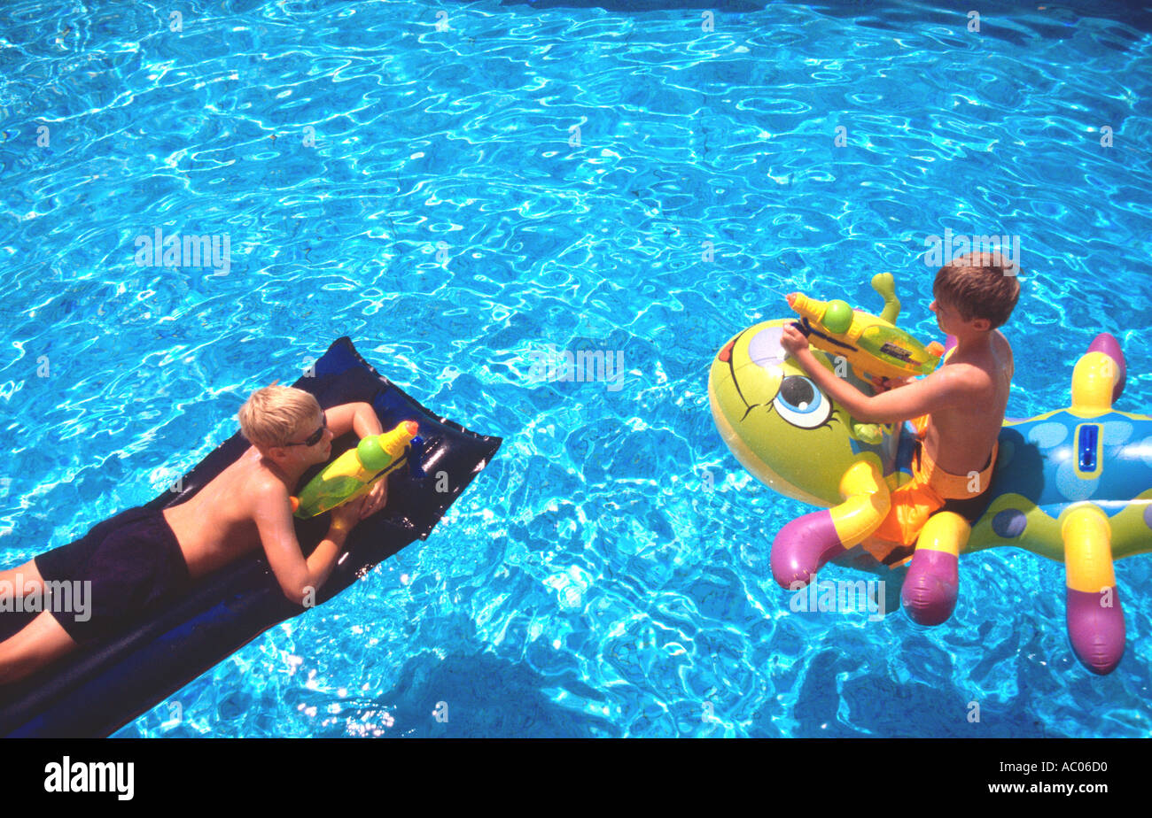 Two Boys Playing On Inflatables In Villa Swimming Pool Provence South Stock Photo Royalty Free