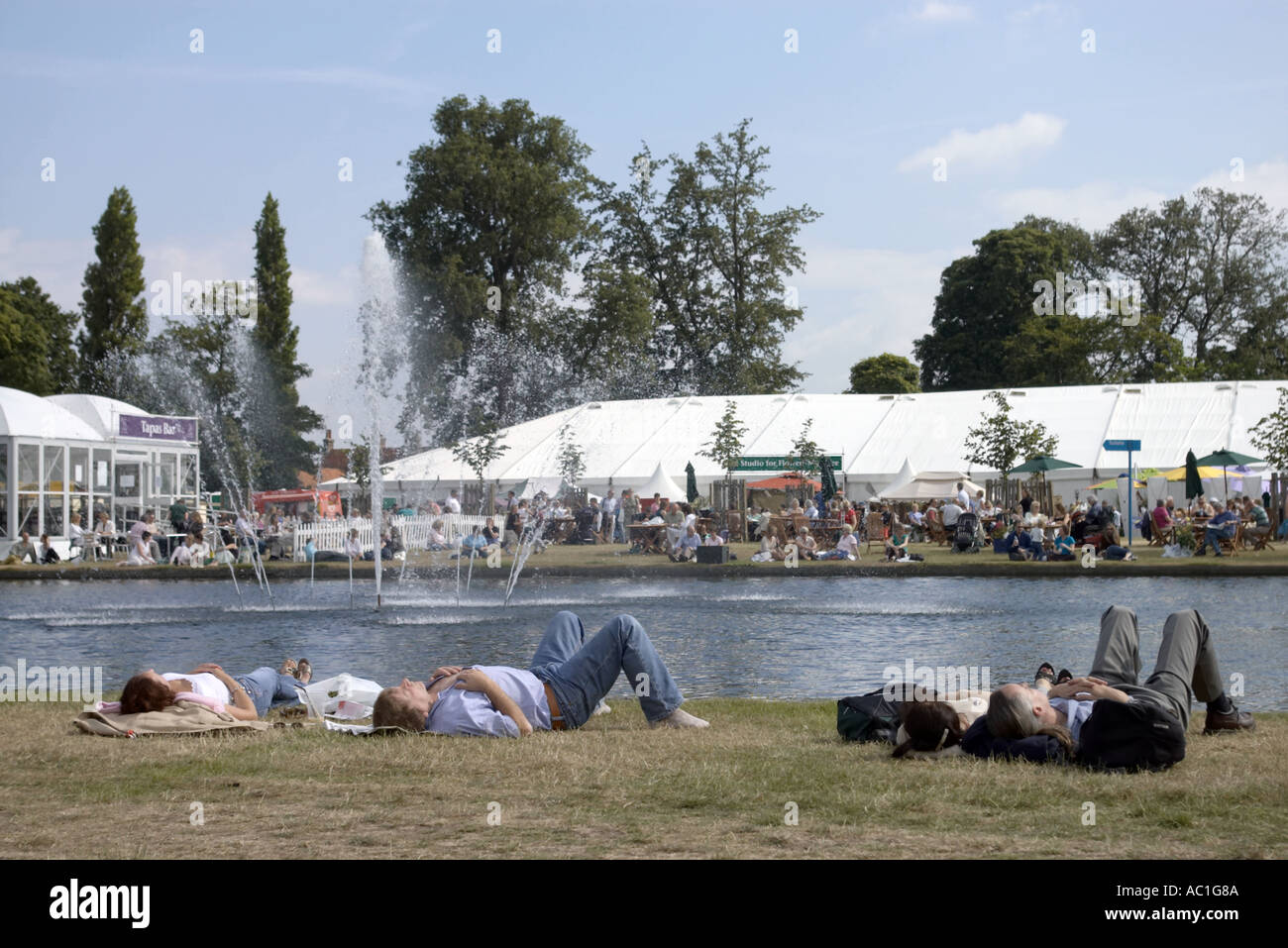 Couples Relax By The Long Water In Home Park At Hampton Court