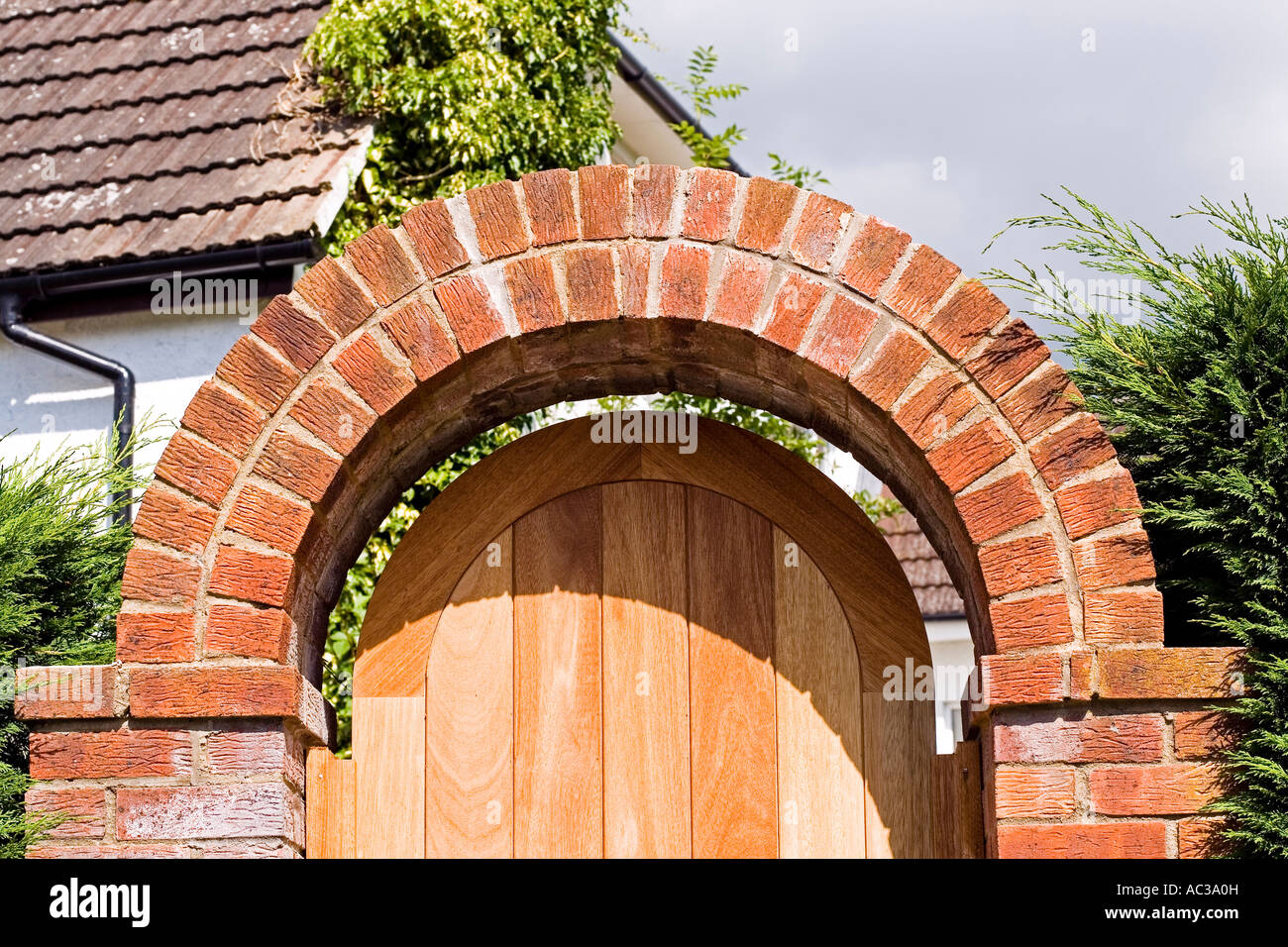 Curved red brick arch over garden gateway with wooden door for Garden gateway