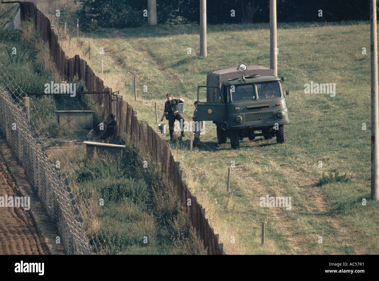 IRON CURTAIN EAST GERMAN BORDER GUARDS FEED DOGS THAT PATROL BETWEEN DOUBLE  FENCE 1989   Stock