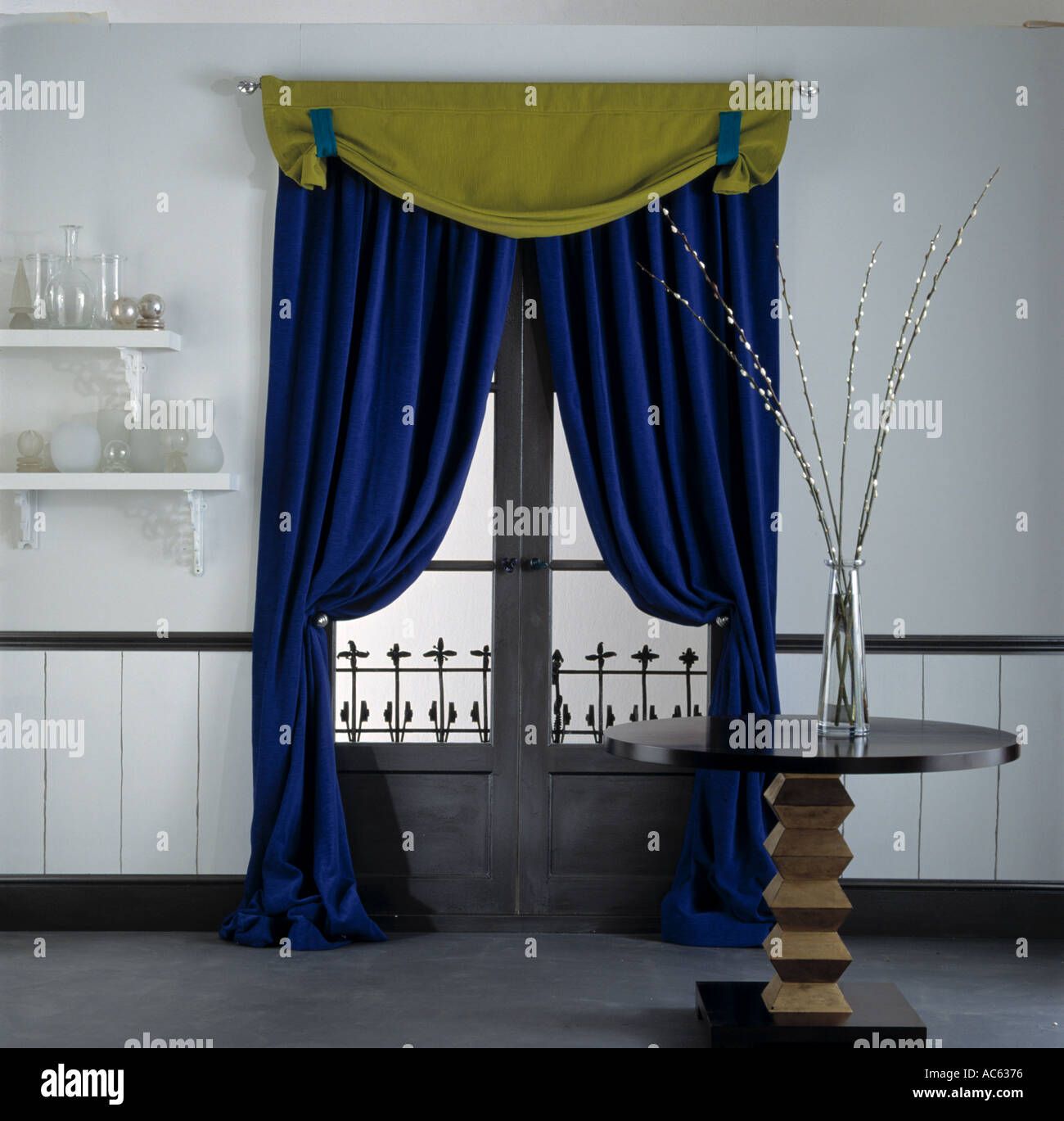 Cobalt blue window treatments - Stock Photo Yellow Pelmet And Rich Blue Velvet Curtains On Window In Dining Room With Vase Of Pussy Willows On Small Circular Pedestal Table