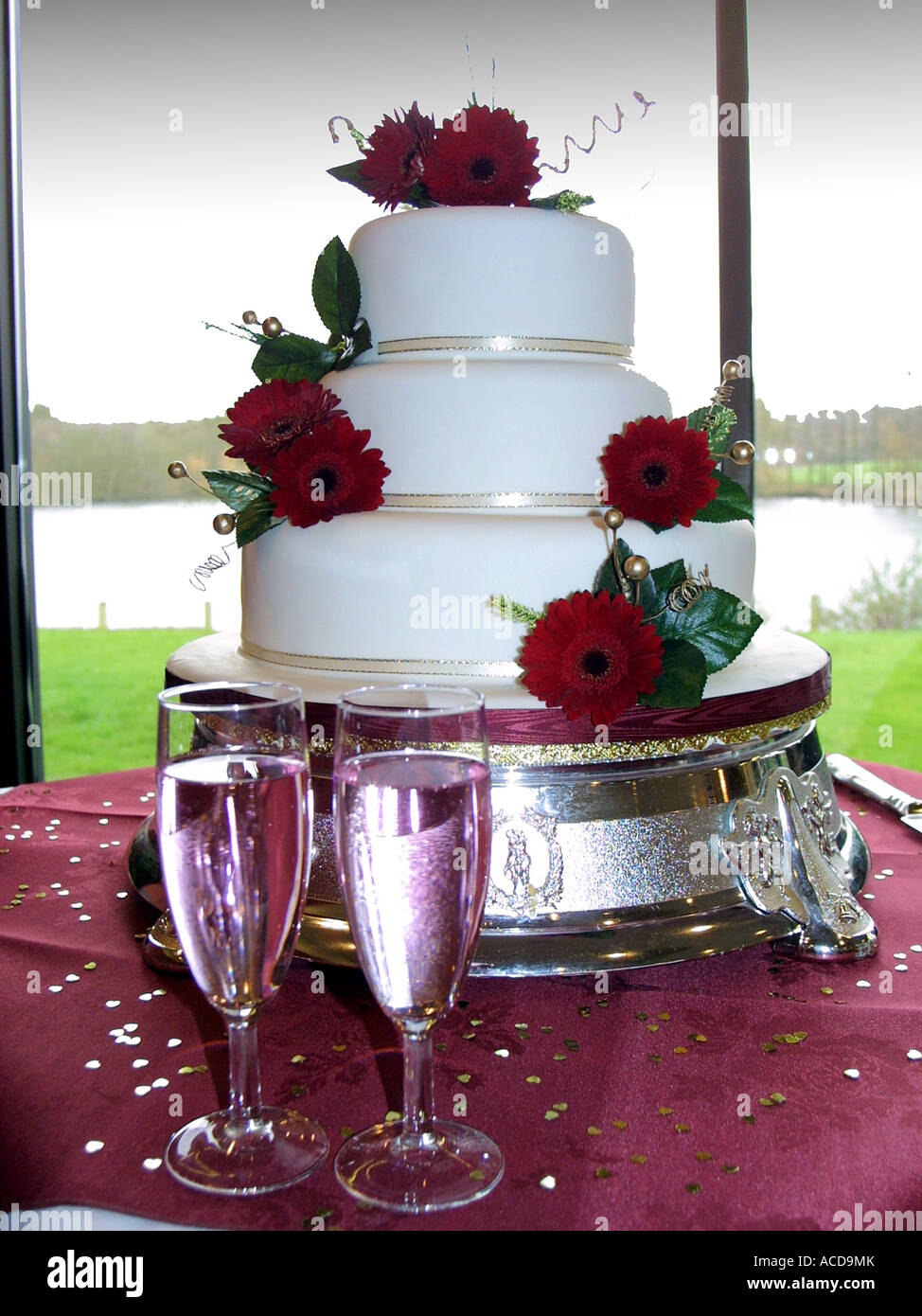 A 3 Tier White Wedding Cake With Red Roses As Decorations And 2 Full Champagne Glasses In The Foreground