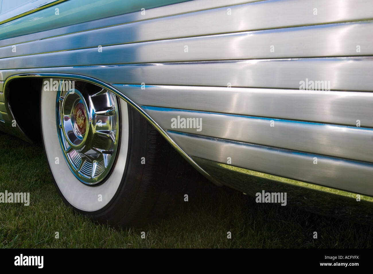 stock photo white wall tire on the back wheel of a cadillac classic car with brushed metal siding decoration on the fender