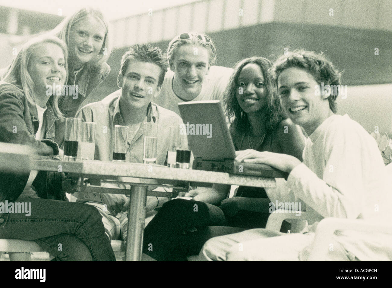 Group of smiling teenagers on caf terrace computer black for The terrace group