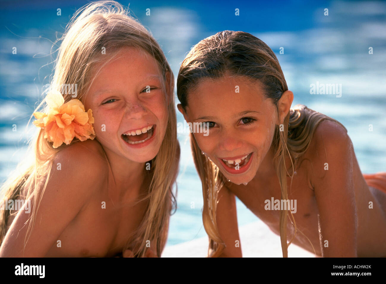 Portrait 2 girls posing bare-chested laughing at the edge of ...