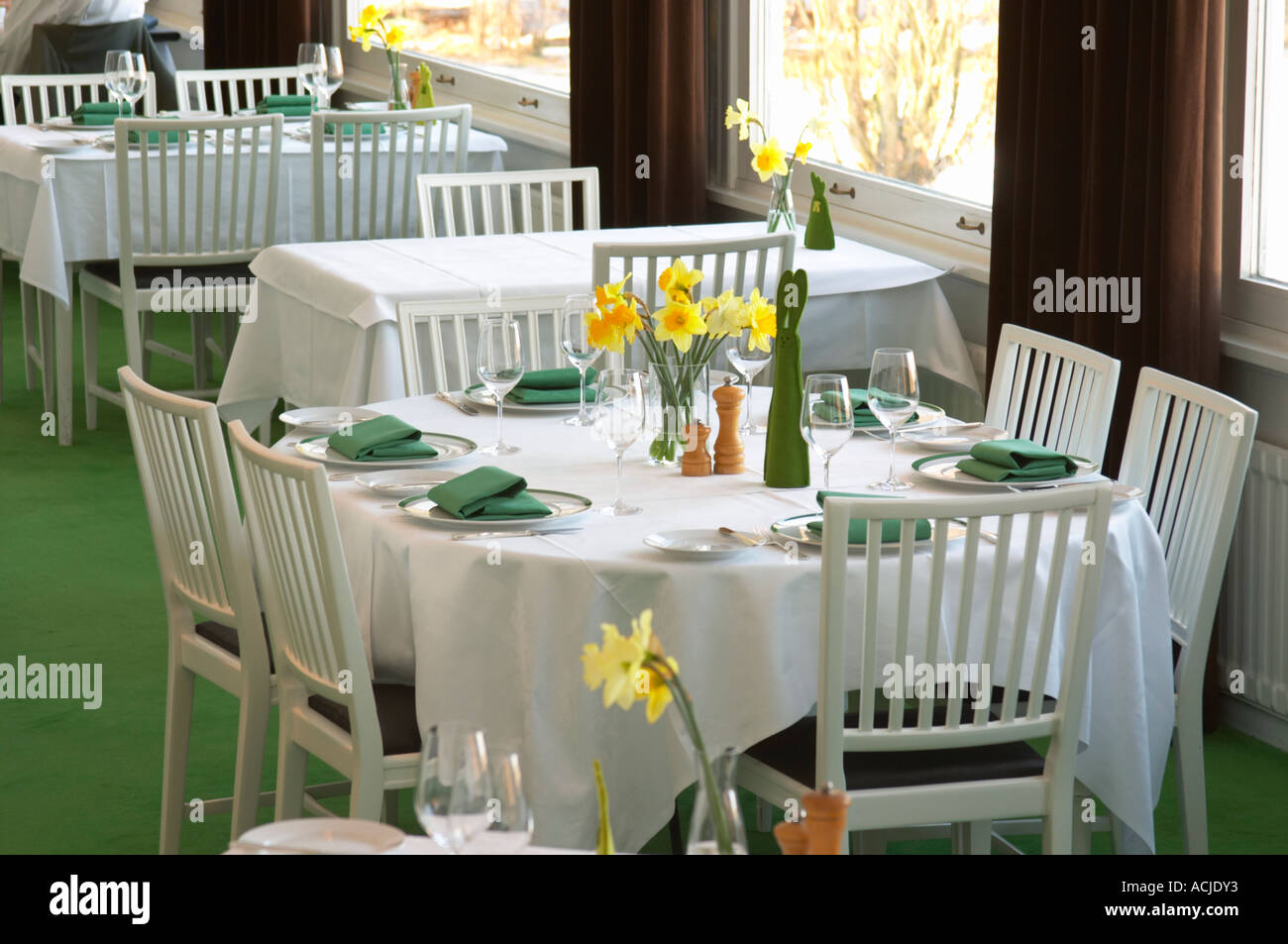 A Restaurant Table With A White Linen Table Cloth Set For Six Persons, With  Plates