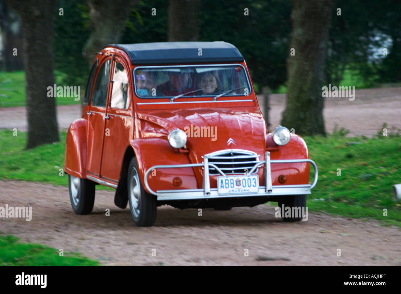 an old red citroen 2cv 2 cv car with a smiling woman driving  elisa stock photo  royalty free