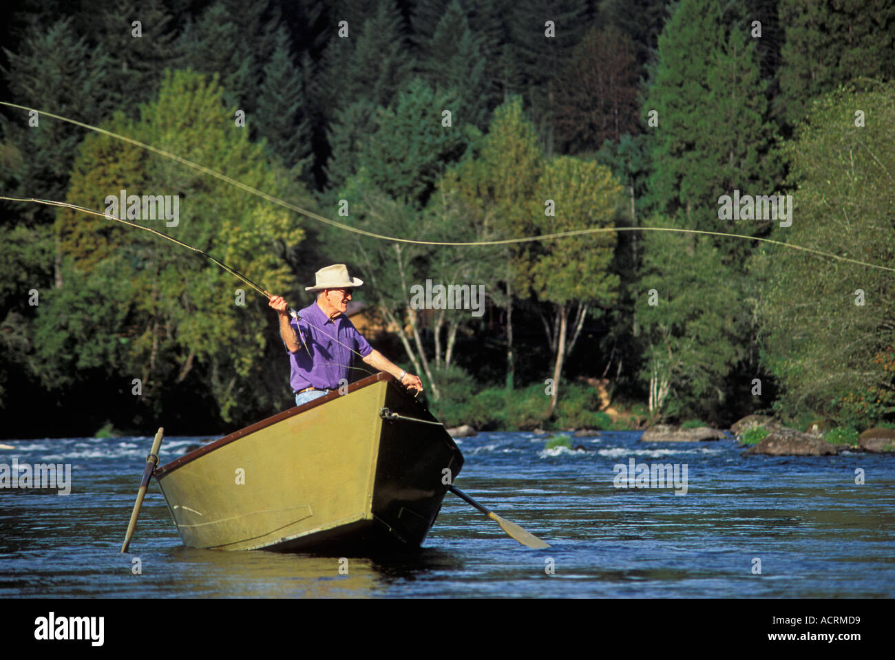 Man fly fishing from a drift boat on the mckenzie river for Drift boat fishing