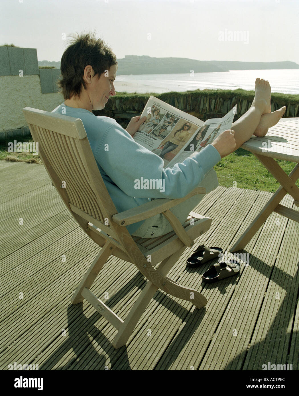 Woman Sitting With Feet On Table On A Deck Chair In The
