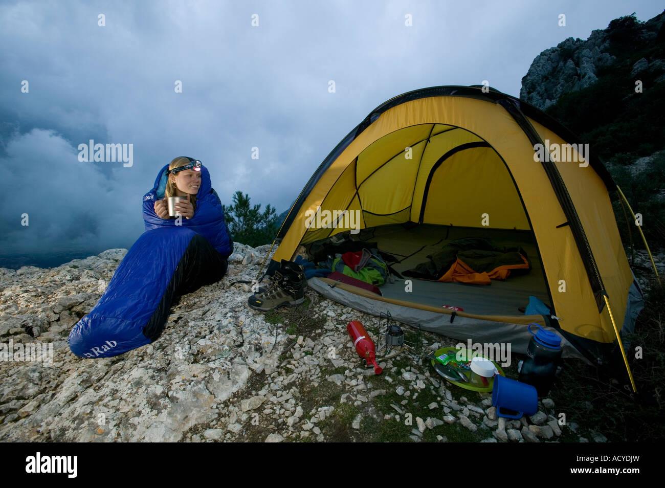 Female backpacker seated in sleeping bag outside tent & Female backpacker seated in sleeping bag outside tent Stock Photo ...